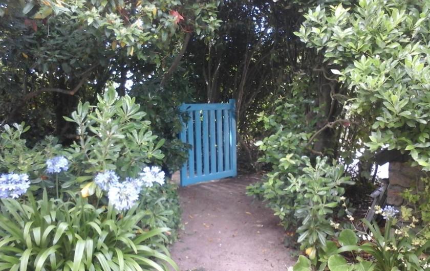 Location de vacances - Villa à Le Pouldu - La barrière bleue ouverte sur les agapanthes fleuries.  au POULDU