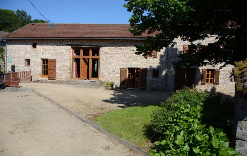 Location de vacances - Gîte à Ambazac - l'ancienne grange aménagée à gauche.  L'aire de pétanque devant