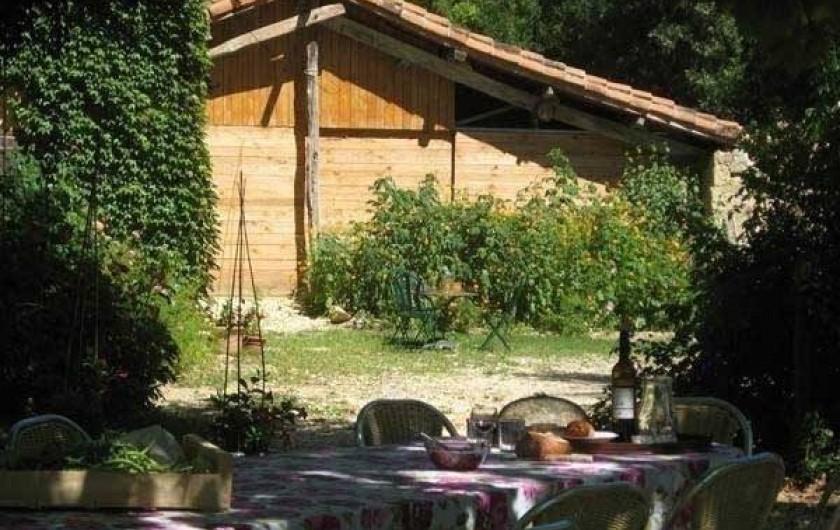 Location de vacances - Maison - Villa à Castéra-Verduzan - la table des repas sous les arbres, au fond la grange avec la cuisine d'été