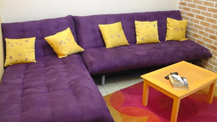 Espace cocooning salon avec clic clac,  méridienne et TV