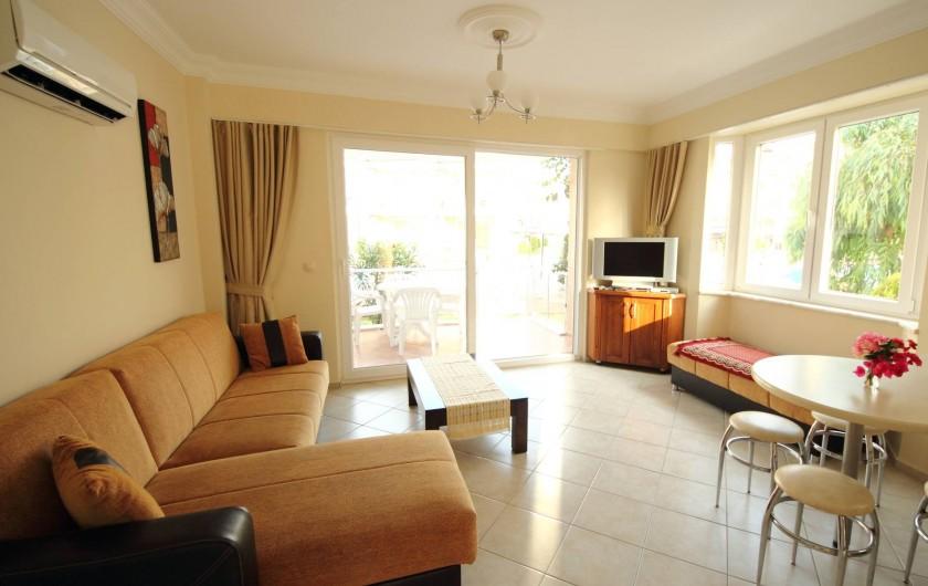 Location de vacances - Appartement à Fethiye - Salon avec vue sur terrasse et piscine au fond