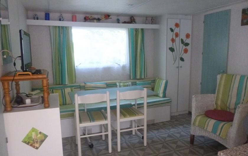 Location de vacances - Bungalow - Mobilhome à Hyères - salon - chambre  2 lits derrière fauteuil porte verte