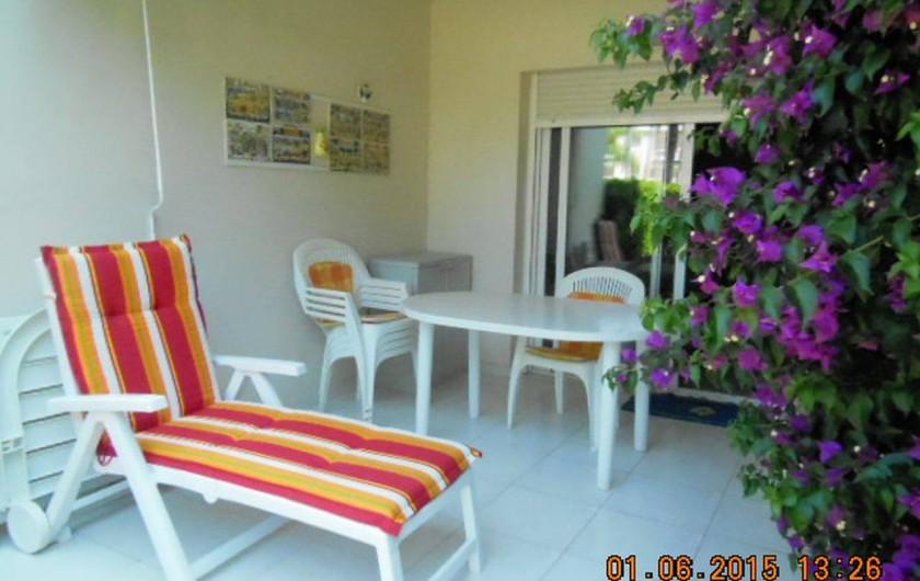 Location de vacances - Appartement à Dénia - la terrasse couverte agrémentée par le bougainvillier en fleurs