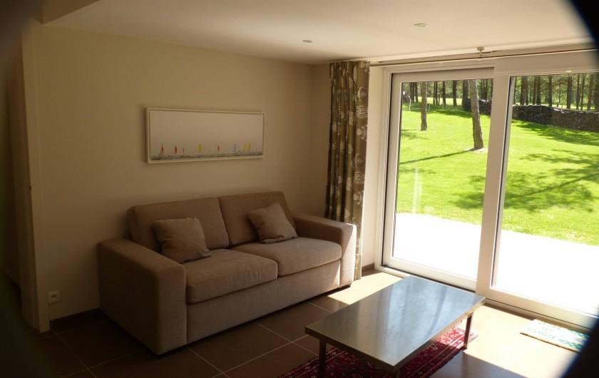 Location de vacances - Appartement à Hardelot-Plage - salon avec le divan lit et la vue sur le jardin et golf
