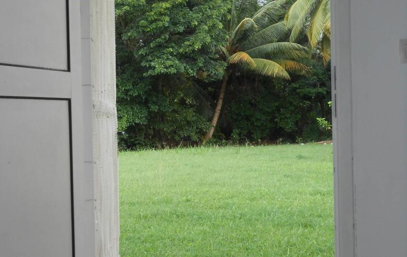 Location de vacances - Appartement à Les Trois-Îlets - vue jardin depuis le canapé, transats disponibles