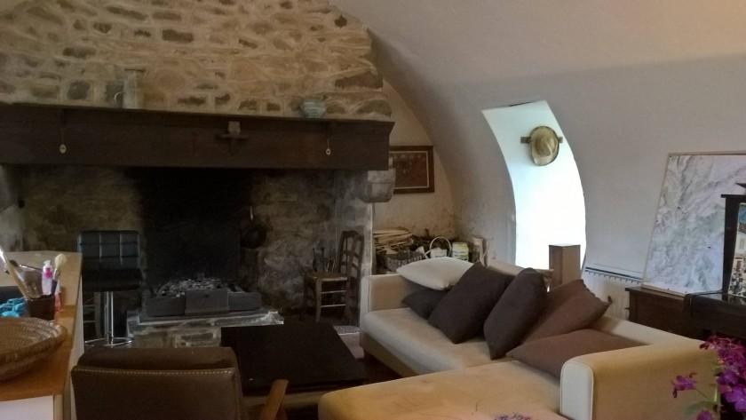 Pièce de vie au rez-de-chaussée : coin salon et grande cheminée (cantou)