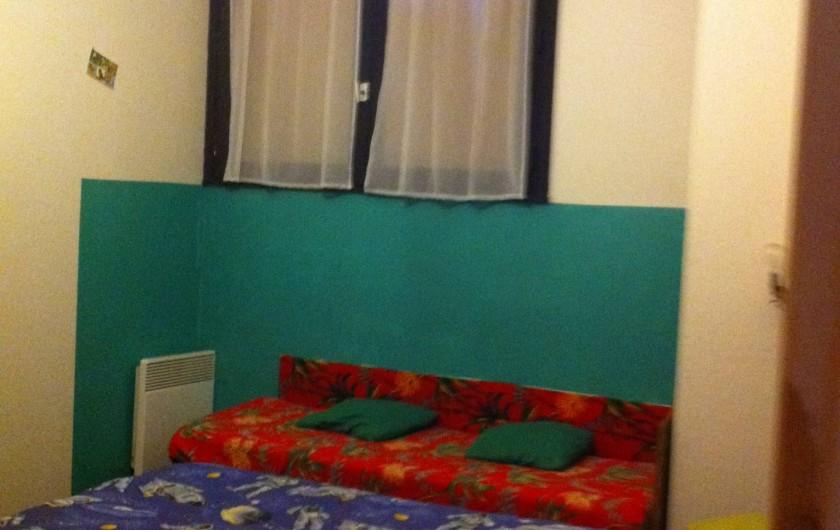 Location de vacances - Appartement à Super Besse - vue en entrant dans la chambre : lit double (bleu)+ lit d'enfant (rouge)