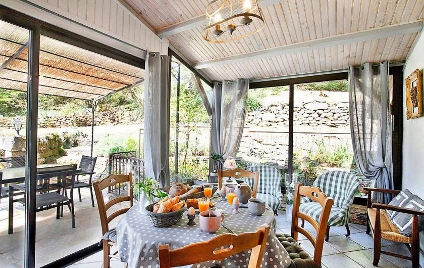 Location de vacances - Villa à Vezac - Véranda vue sur le bassin à carpes et sa terrasse couverte.