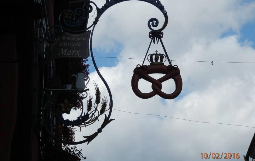 Location de vacances - Mas à Eguisheim - enseigne du boulanger du village avec le célèbre bretzel