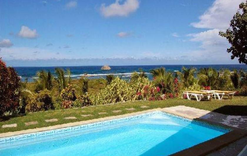 Location de vacances - Villa à Saint-François - Façade principale et terrasse vue sur mer. Meubles extérieurs et piscine.