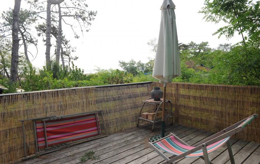 Location de vacances - Chalet à Le Cap Ferret - Coin droit de la terrasse , parasol chaises longues .