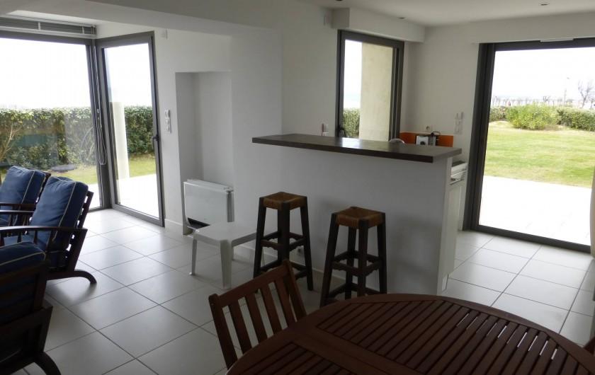 Location de vacances - Appartement à Soorts-Hossegor - appartement n°2: : coin repas ; cuisine derrière le bar donnant sur le jardin