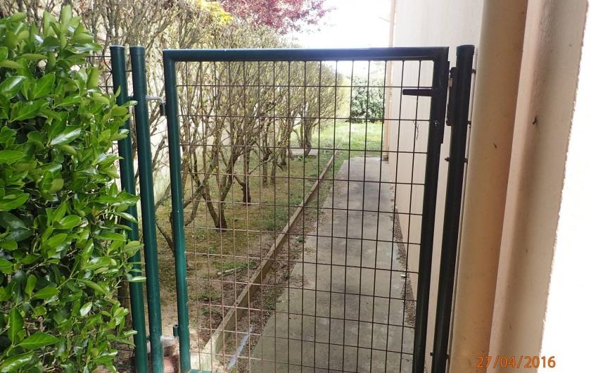 Location de vacances - Villa à Saint-Hilaire-de-Riez - passage sur le côté de la maison, un portillon fermé,  avec une clé