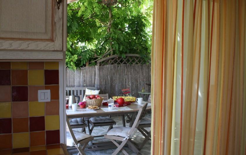 Location de vacances - Gîte à Lafrançaise - Accès de la cuisine à la terrasse ombragée par une glycine.