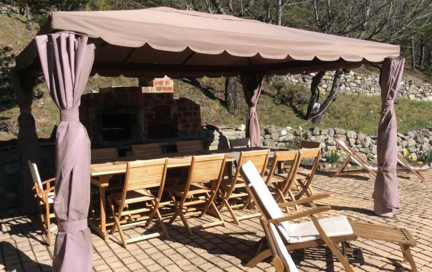 Location de vacances - Chalet à Barcelonnette - Le coin repas  accueille 16 personnes. Barbecue et four à pizzas, transats.