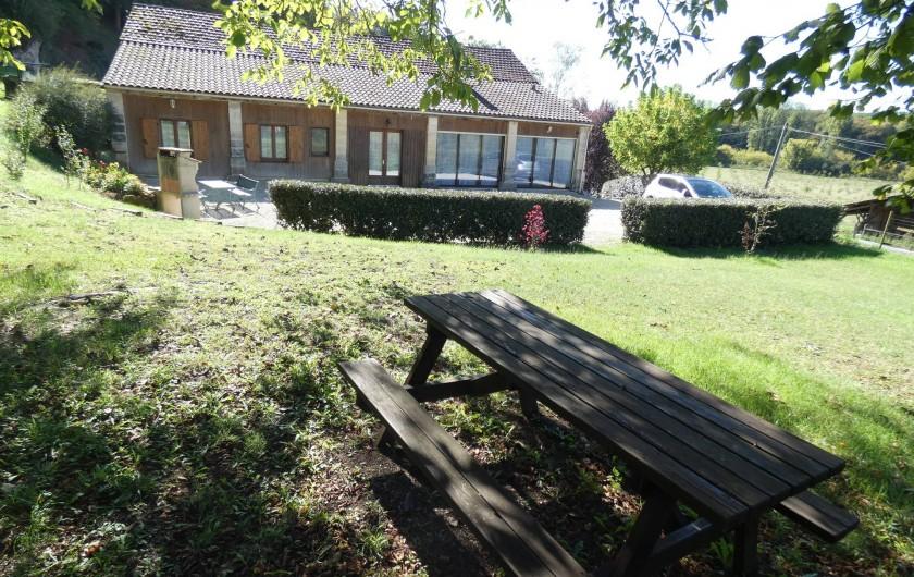 Location de vacances - Gîte à Tursac - façade du gîte vue du coin pic nic, à l'ombre des arbres