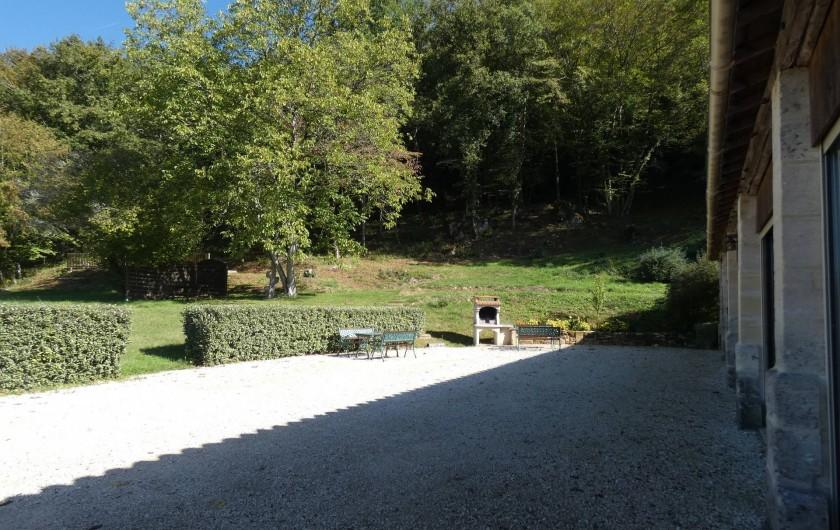 Location de vacances - Gîte à Tursac - terrasse devant le gîte avec le barbecue et ses tables
