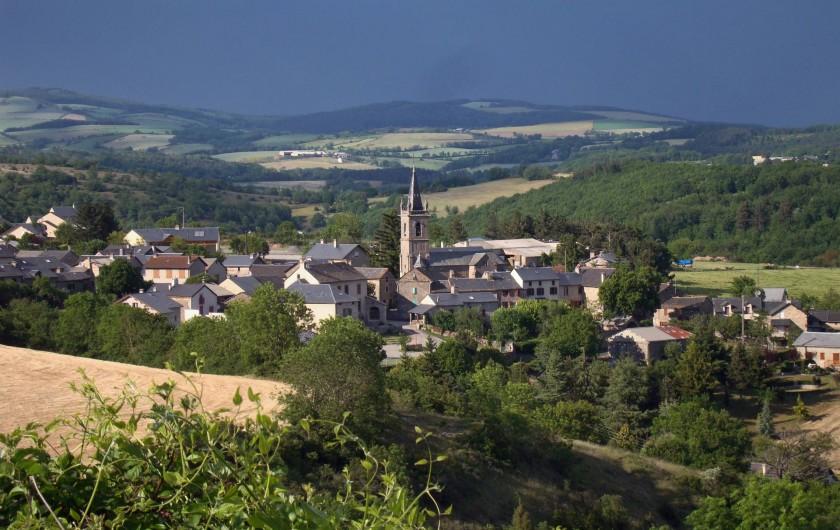Location de vacances - Chambre d'hôtes à Saint-Laurent-de-Lévézou - Vue sur le village St Laurent de Lévézou au détour d'un chemin