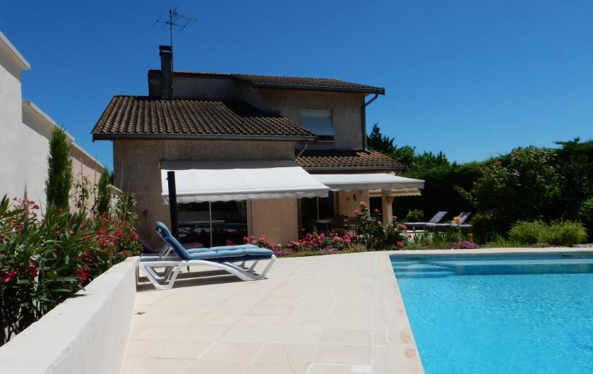 Location de vacances - Villa à Caluire-et-Cuire - le mur au lauriers rose et les stores de la maison