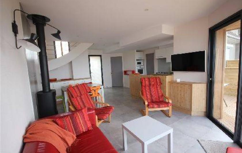 Location de vacances - Gîte à Langrune-sur-Mer - séjour coin cuisine à droite, poêle séparant la table et le salon.