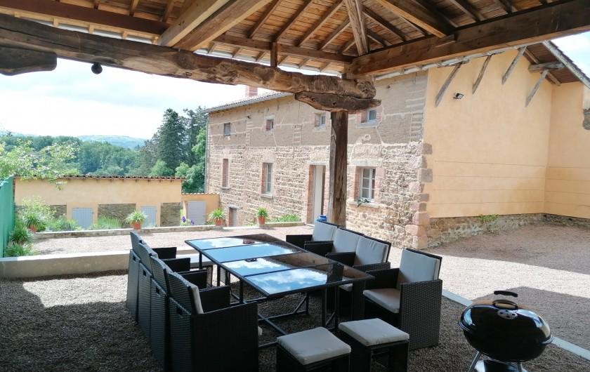 """Location de vacances - Gîte à Pomeys - Vue depuis le """"chapi"""" avec mobilier de jardin et barbecue."""