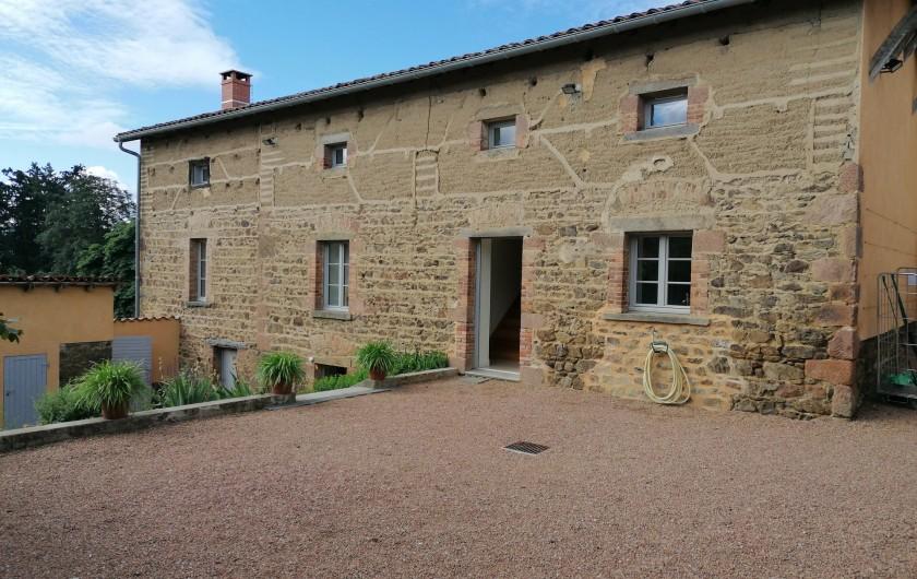 Location de vacances - Gîte à Pomeys - La façade nord du gîte dans la cour en pierre et pisé.