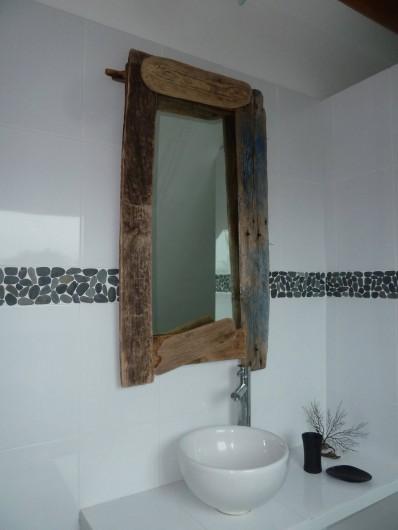 Location de vacances - Appartement à Pénestin - détail de la salle de bain, miroir en bois flotté et frise de galets