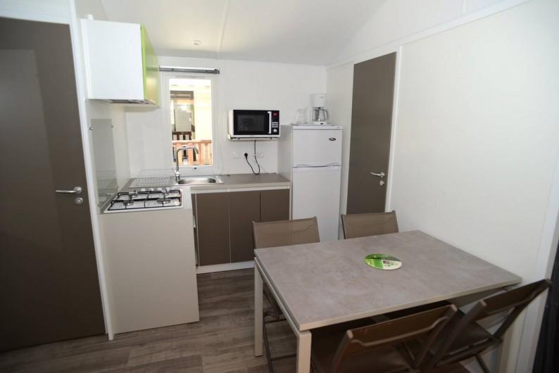 """Location de vacances - Bungalow - Mobilhome à Le Camp - Vue sur la pièce à vivre du mobil home """"Azur"""" : coin cuisine et espace repas"""