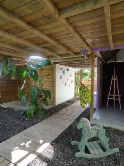 Location de vacances - Gîte à Saint-François - Pergola où sont suspendus les régimes de bananes  cueillis dans le jardin