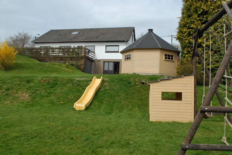 Location de vacances - Gîte à Malmedy - Le jardin avec la cabane barbecue et les jeux pour enfants.