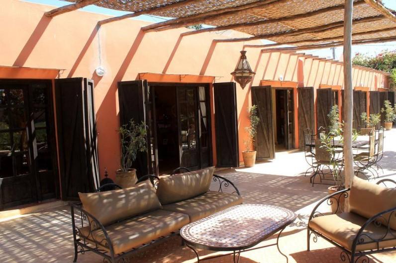 Location de vacances - Chambre d'hôtes à Agadir - coin detente et , plus loin, table pour les petits dejeuners