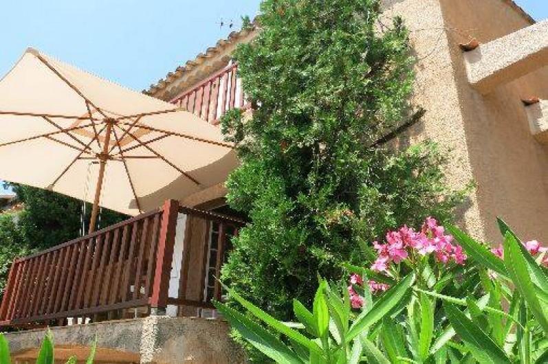 Location de vacances - Mas à Agay - Vue de la terrasse avec parasol depuis le jardin