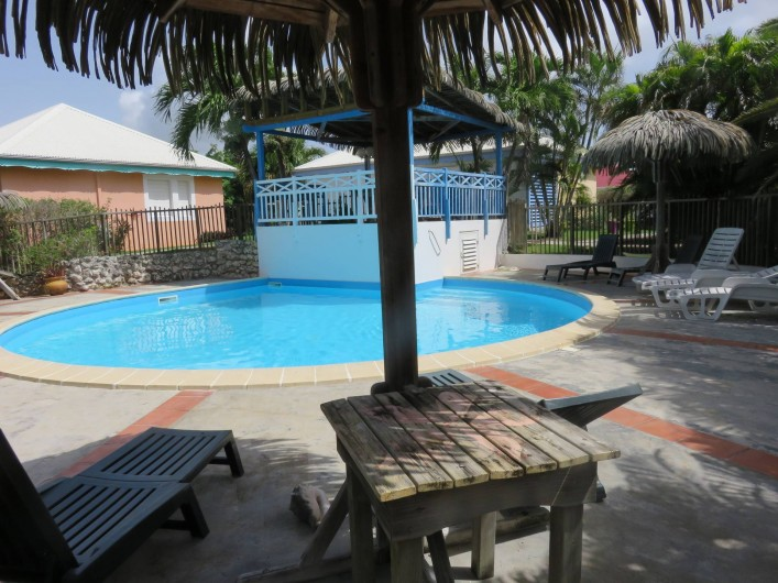 Location de vacances - Gîte à Saint-François - la piscine et son carbet. Transats & parasol