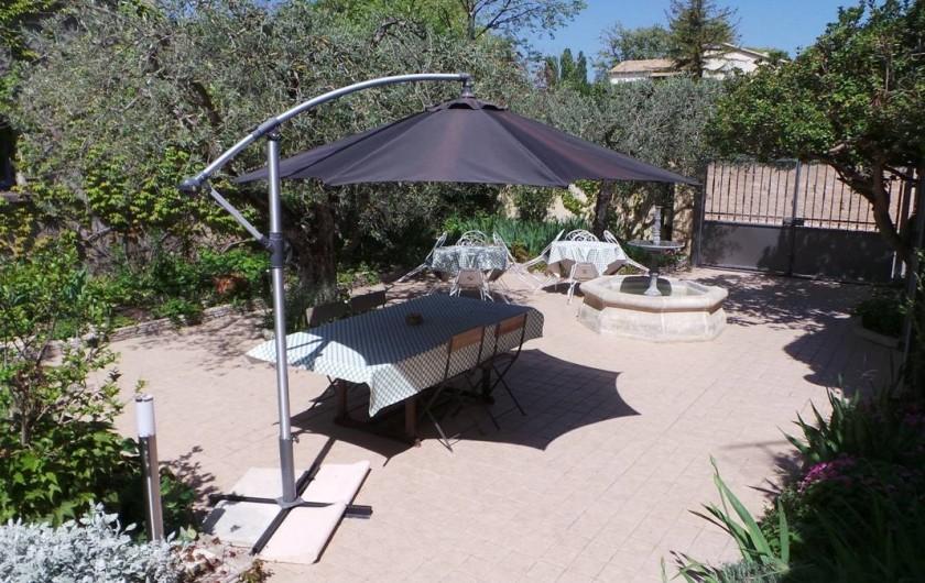 Location de vacances - Villa à Bezouce - Terrasse du gîte avec sa grande table, son parasol et deux salons de jardin