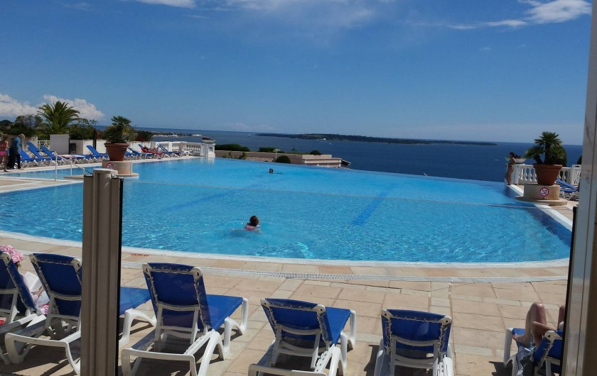 Location de vacances - Appartement à Cannes - Piscine vue depuis la terrasse du RESTAURANT. Au fond les  iles de LERIN.