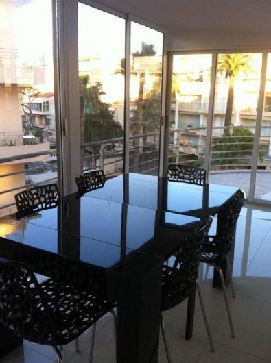 Location de vacances - Appartement à Cannes - salle à manger dans véranda ouverte