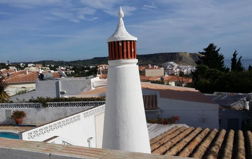 Location de vacances - Chalet à Luz - Vue depuis le solarium (piscine à gauche, toit/cheminée, paysage/mer