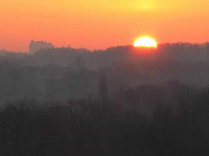 Location de vacances - Gîte à Villeréal - Vue de la terrasse - Levé de soleil sur le château de Biron