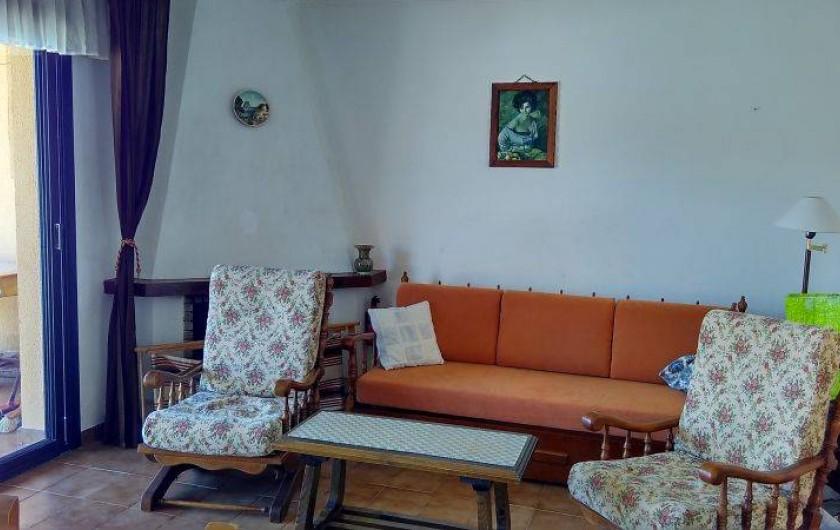 Location de vacances - Appartement à Roses - Le salon, avec la cheminée, le canapé, 2 fauteuils et table basse.