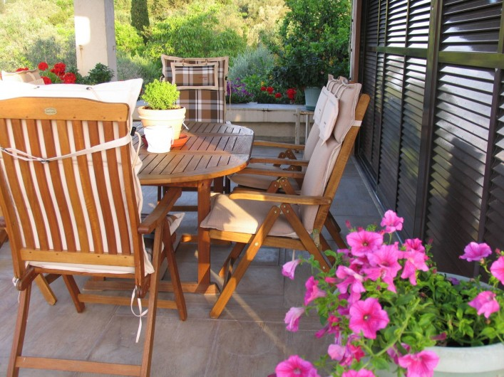 Location de vacances - Villa à Corfu - Veranda with wooden furniture and flower bed.