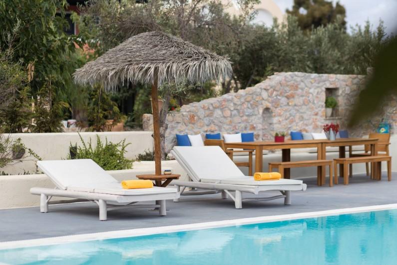 Location de vacances - Villa à Thera - Chaises longues dans la piscine. Salle à manger a l'exterieur.