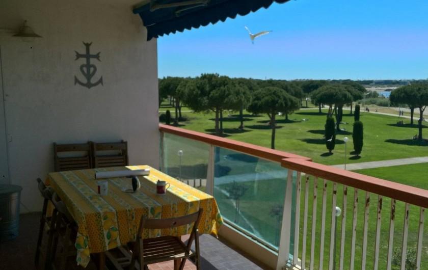 Location de vacances - Appartement à Le Grau-du-Roi - vue du balcon sur l'espace de verdure, avec au fond Port-Camargue
