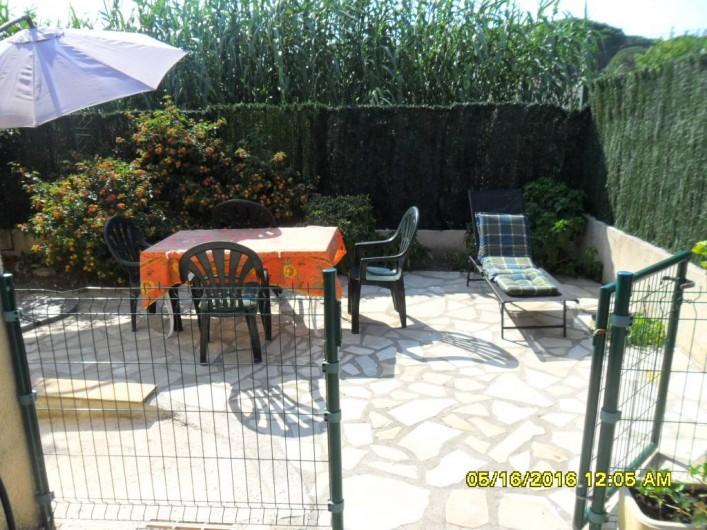 Location de vacances - Appartement à Sainte-Maxime - Accès jardin avec grillage de séparation + transat + table extérieure.
