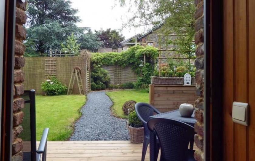 Location de vacances - Gîte à Bertrix - Le jardin vue de l'intérieur du gîte.  Le chemin rejoins le parking privé