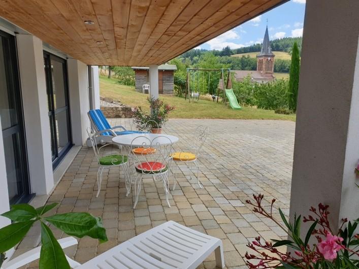 Location de vacances - Appartement à Valsonne - Terrasse couverte du Gite avec vue sur l'église et les 4 éoliennes du Rhone