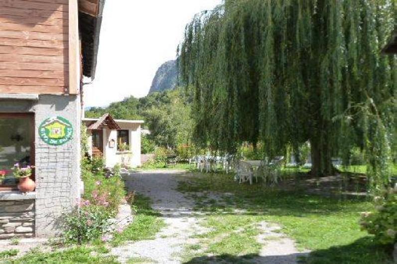 Location de vacances - Gîte à Saint-Clément-sur-Durance - Au fond, l'entrée du gîte. Salon de jardin sous le saule pleureur.