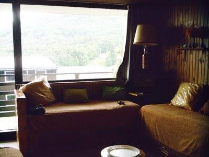 Location de vacances - Appartement à Super Besse - séjour : baie vitrée, lits, TV