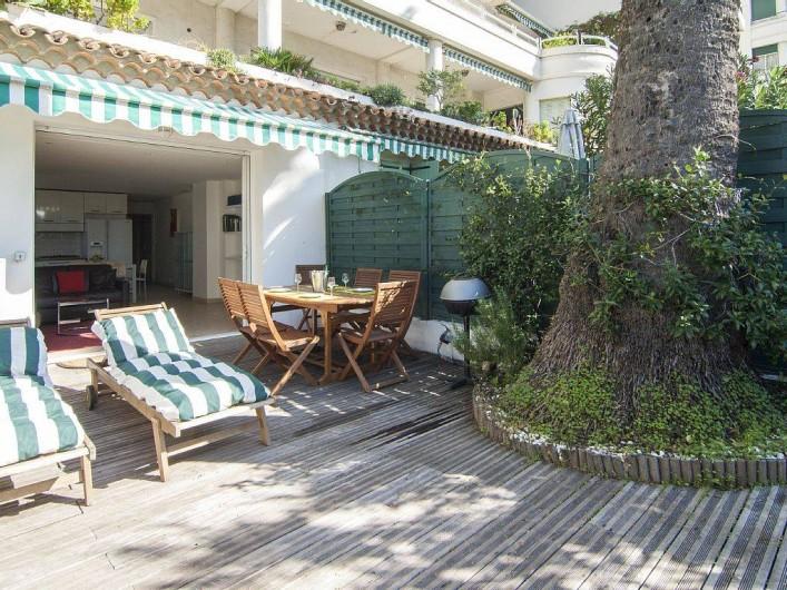 Location de vacances - Appartement à Cannes - Le jardin / terrasse : coin chaises longues, coin repas avec BBQ