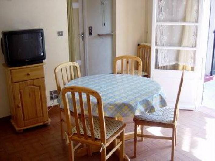 Location de vacances - Villa à Antibes - La salle à manger et la porte fenêtre ouvrant sur la terrasse