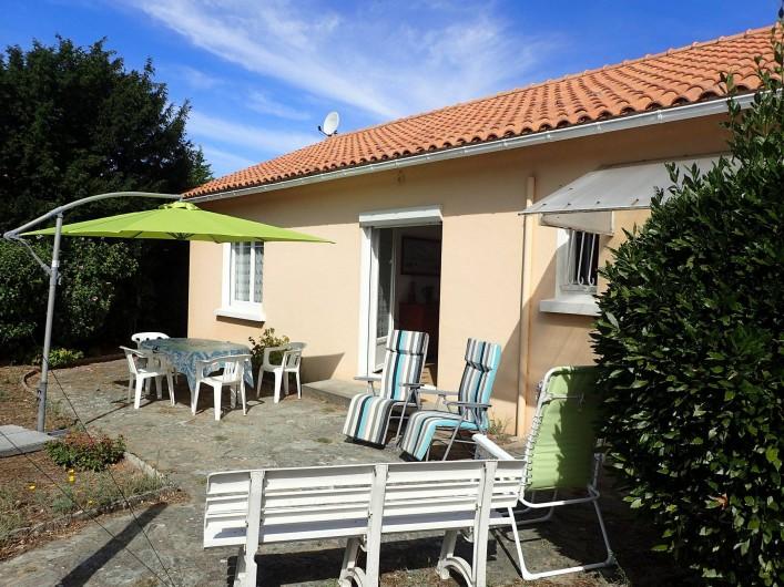 Location de vacances - Villa à Saint-Hilaire-de-Riez - terrasse côté jardin avec son salon de jardin son parasol et ses transats